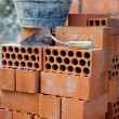 Bricks stacked, trowel and cube in the work - Stock Photo