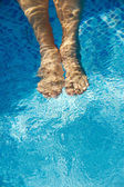 Feet refreshing in swimming pool — Stock Photo