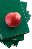 A red apple red on a green book — Stock Photo