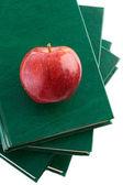 Uma maçã vermelha vermelha em um livro verde — Foto Stock