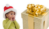 Surprised baby girl with one gift of Christmas — Stock Photo
