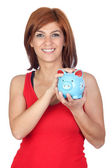 Beautiful redhead girl with a blue piggy-bank — Stock Photo