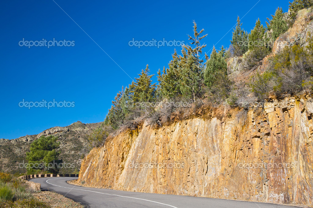 Mountain road with sharp curve with blue sky background — Stock Photo #9440849