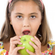 Stock Photo: Adorable girl with flowered dress eating a apple