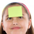 Adorable girl squint with post-it in her front — Stock Photo