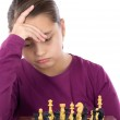 Worried little girl playing chess — Stock Photo #9497421