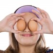 Adorable girl with two eggs on his eyes — Stock Photo #9497612
