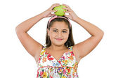 Adorable girl with flowered dress with a apple — Stock Photo
