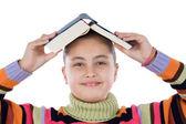 Fille adorable avec un livre sur la tête — Photo