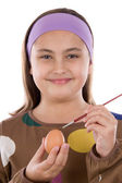 Adorable girl adorning Easter eggs — Stock Photo