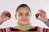Cute girl holding two strawberries — Stock Photo