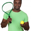Attractive african man with a tennis racket — Stock Photo