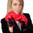 Challenging business woman with boxing gloves - Stock Photo