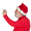 Stock Photo: Funny Santa Claus writing with a pen