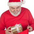 Funny Santa Claus taking a gift from his sack — Stock Photo