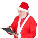 Santa Claus writing on clipboard — Stock Photo