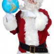 Santa Claus pointing at a globe — Stock Photo