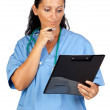 Happy doctor woman with clipboard thinking — Stock Photo #9506859