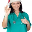 Attractive doctor woman with Christmas hat saying Ok — Stock Photo #9507475