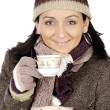 Foto Stock: Attractive lady sheltered for winter drinking tecup