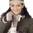 Attractive lady sheltered for winter drinking tecup — Stock fotografie #9507865