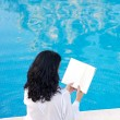 Attractive lady reading in the swimming pool — Stock Photo #9508023