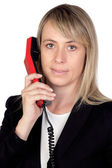 Blonde businesswoman with a red phone — Stock fotografie