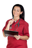 Happy doctor woman with clipboard thinking — Stock Photo