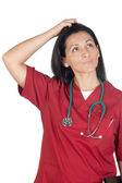 Happy doctor woman with burgundy clothing thinking — Stockfoto
