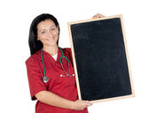 Happy doctor woman with blank blackboard — Stockfoto