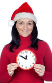 Beautiful girl with Christmas hat and a clock — Stock Photo
