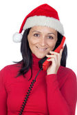Beautiful girl with Christmas hat to phone — Stock Photo