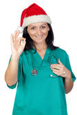 Attractive doctor woman with Christmas hat saying Ok — Stock Photo