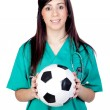 Attractive brunette doctor with soccer ball - Stock Photo