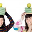 Two attractive girls with books and apple in the head - Stock Photo