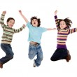 Three happy children jumping at once — Stock Photo