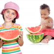 Baby and girl eating watermelon - Stock Photo