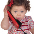 Funny baby girl with red telephone — Stock Photo #9628884
