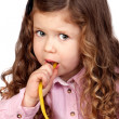 Adorable baby with pink shirt eating goodies - Stock Photo