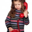 Adorable baby with a red telephone — Stock Photo #9628945