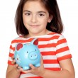 Brunette little girl with a blue moneybox - Stock Photo