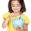 Brunette little girl with a blue moneybox — Stock Photo #9629937