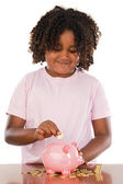 Adorable african girl putting a coin in a piggbank — Stock Photo