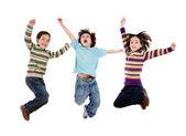Tři šťastné děti skákání najednou — Stock fotografie