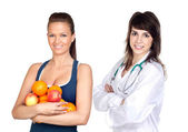 Young pretty girl with many fruits and nutritionist — Stock Photo