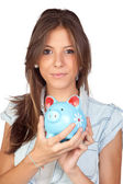 Beautiful girl with a blue piggy-bank — Stock Photo