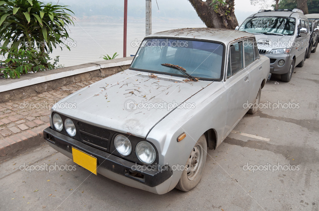 An old car standing near the pavement in the city of Luang Prabang, Lao \'s Democratic Republic. — Stock Photo #9418948