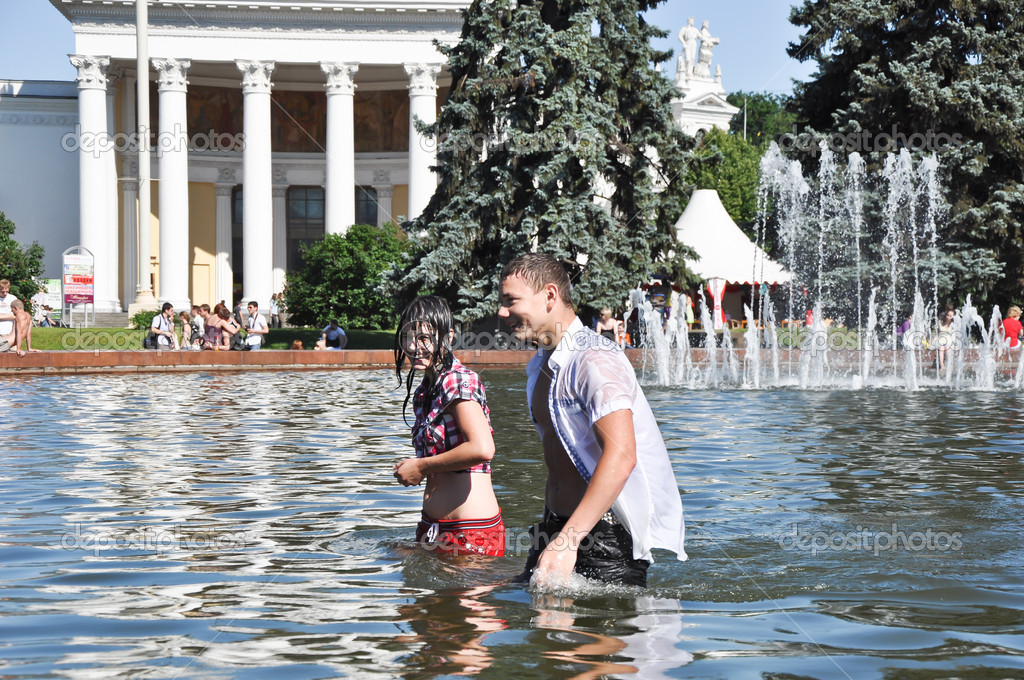 Young couple walking out of a public fountain after swimming, cheerful and cooled down on a hot sunny day. — Stok fotoğraf #9859585