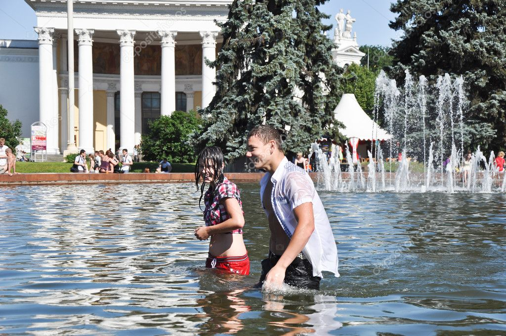 Young couple walking out of a public fountain after swimming, cheerful and cooled down on a hot sunny day.  Photo #9859585