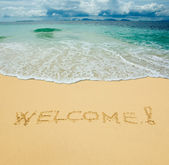 Welcome written in a sandy tropical beach — Stock Photo